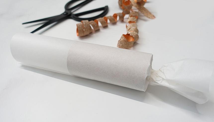 Ein halbfertig gebasteltes Knallbonbon aus Butterbrotpapier von Toppits.