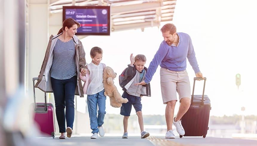 Fröhliche Familie mit Koffern am Bahnhof