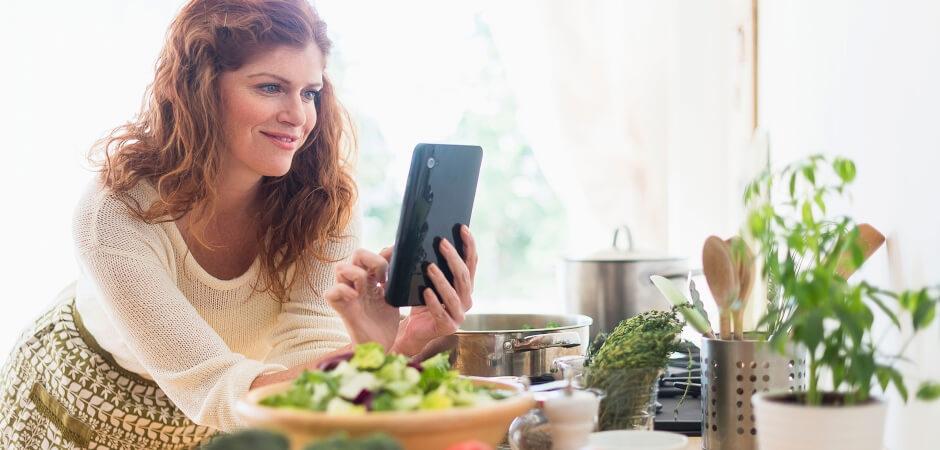 Fröhliche Frau mit Smartphone in der Küche.