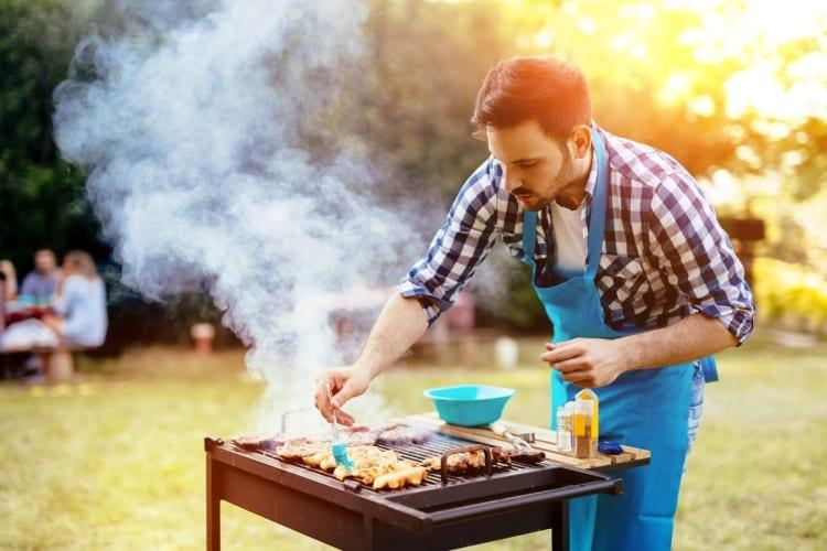 Mann grillt im Garten