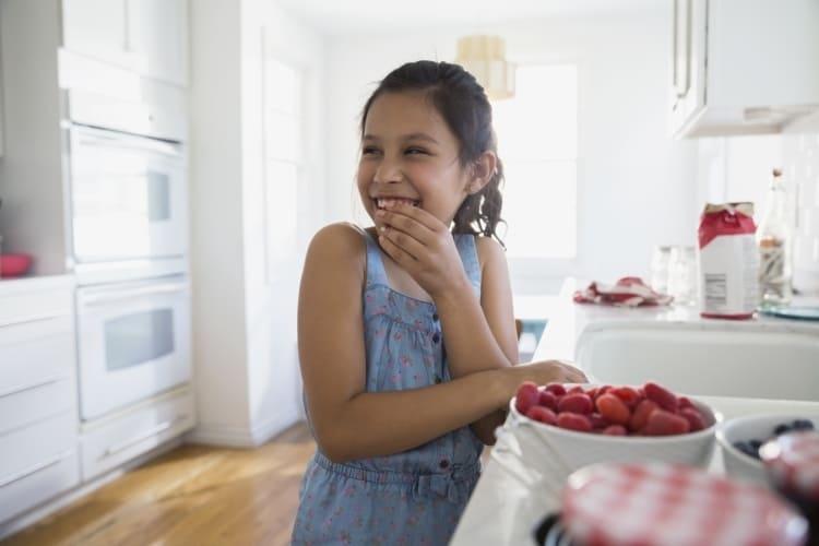 Mädchen in der Küche mit einer Schale Himbeeren und Frischhaltefolie.