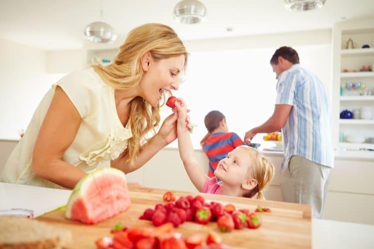 Mutter und Kind naschen frische Erdbeeren