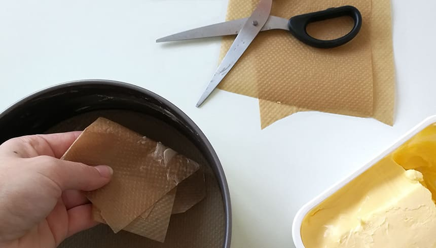 Die Springform wird mit Hilfe von Backpapier eingefettet