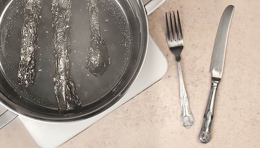 Angelaufenes Silberbesteck in Toppits® Alufolie eingewickelt im Topf