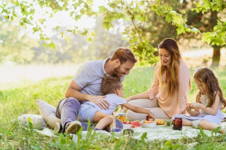 Eine glückliche Familie isst Brote aus Butterbrot-Tüten.