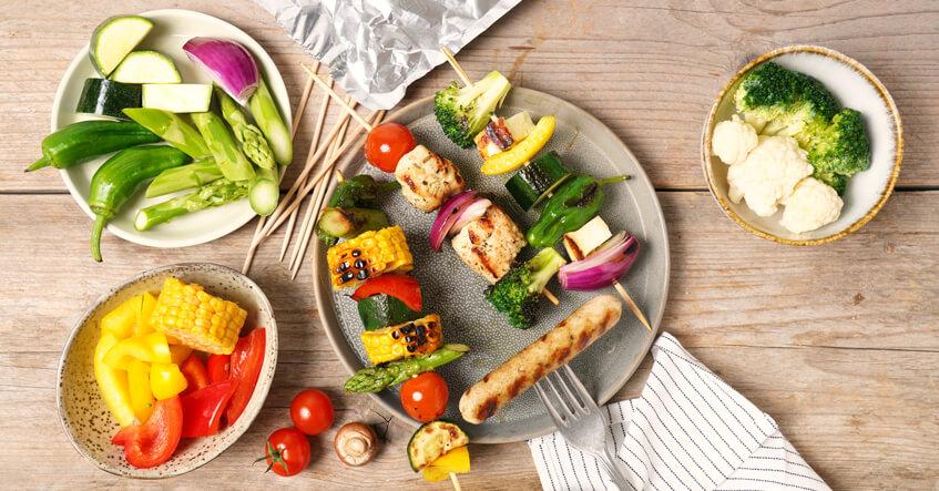Gemüse, Fleisch und Grillkäse im bunten Mix auf Grillspießen aus Holz
