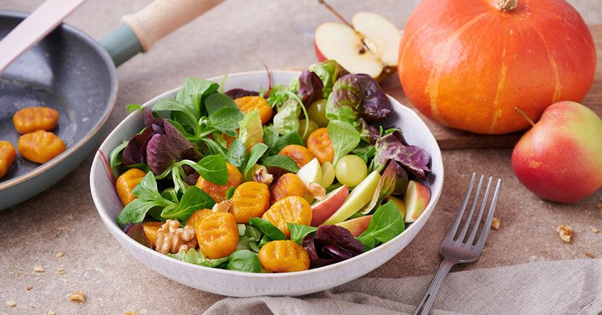 Angebratene Kürbis-Gnocchi auf buntem Salat