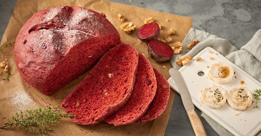 Rote Beete Brot auf Backpapier mit Ziegenkäse auf dem Brett