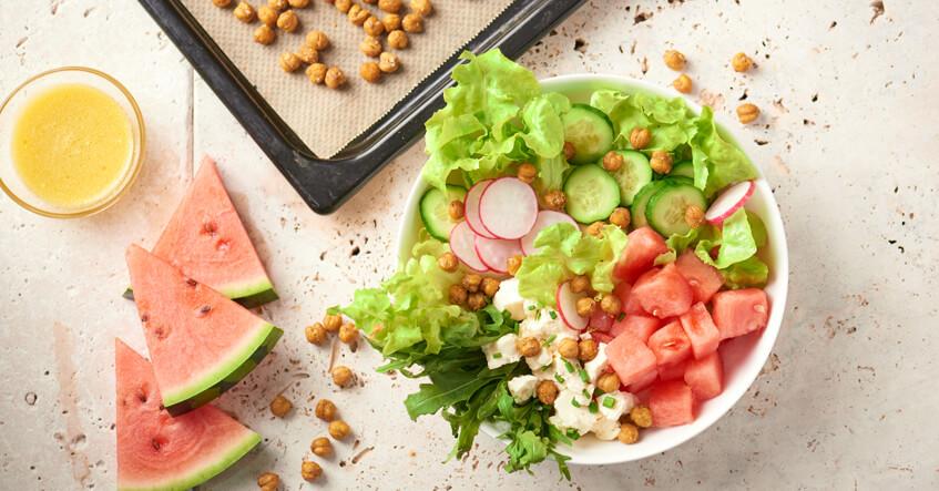 Geröstete Kichererbsen auf Backblech und Sommersalat in der Bowl